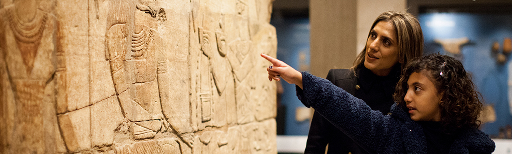 A young girl and her mother look at Egyptian reliefs in a museum gallery