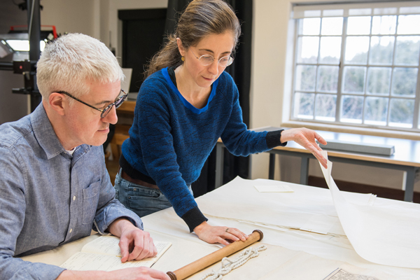 Conservation staff analysing a scroll in the studio