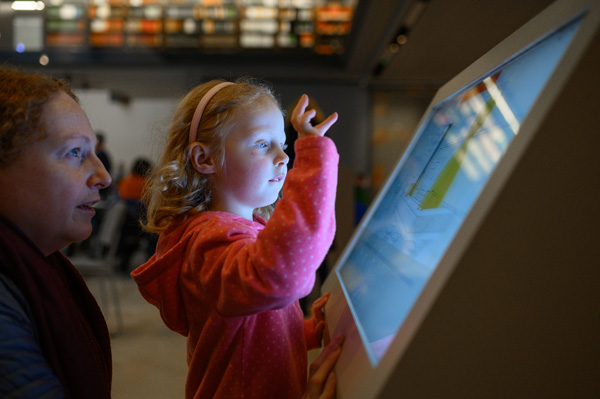 Child interacting with one of the digital displays during the  'Alice in Typhoidland' exhibition
