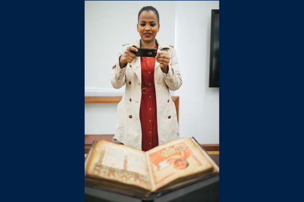 Visitor bringing one of the sacred Ge'ez manuscripts of Ethiopia and Eritrea to life on her phone