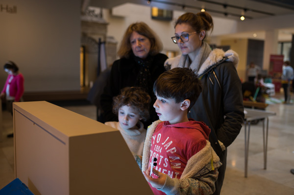 Family interacting with one of the digital displays during the 'Alice in Typhoidland' exhibition