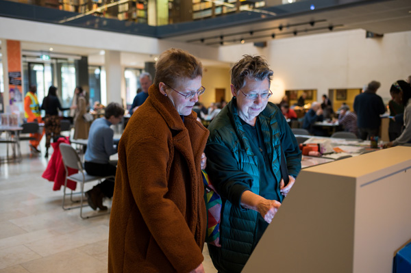 Visitors exploring a digital display at the  'Alice in Typhoidland' exhibition