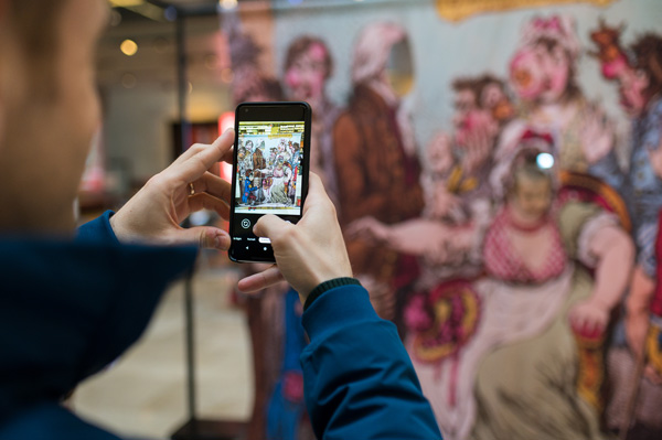 Visitor exploring displays via a phone app during the  'Alice in Typhoidland' exhibition