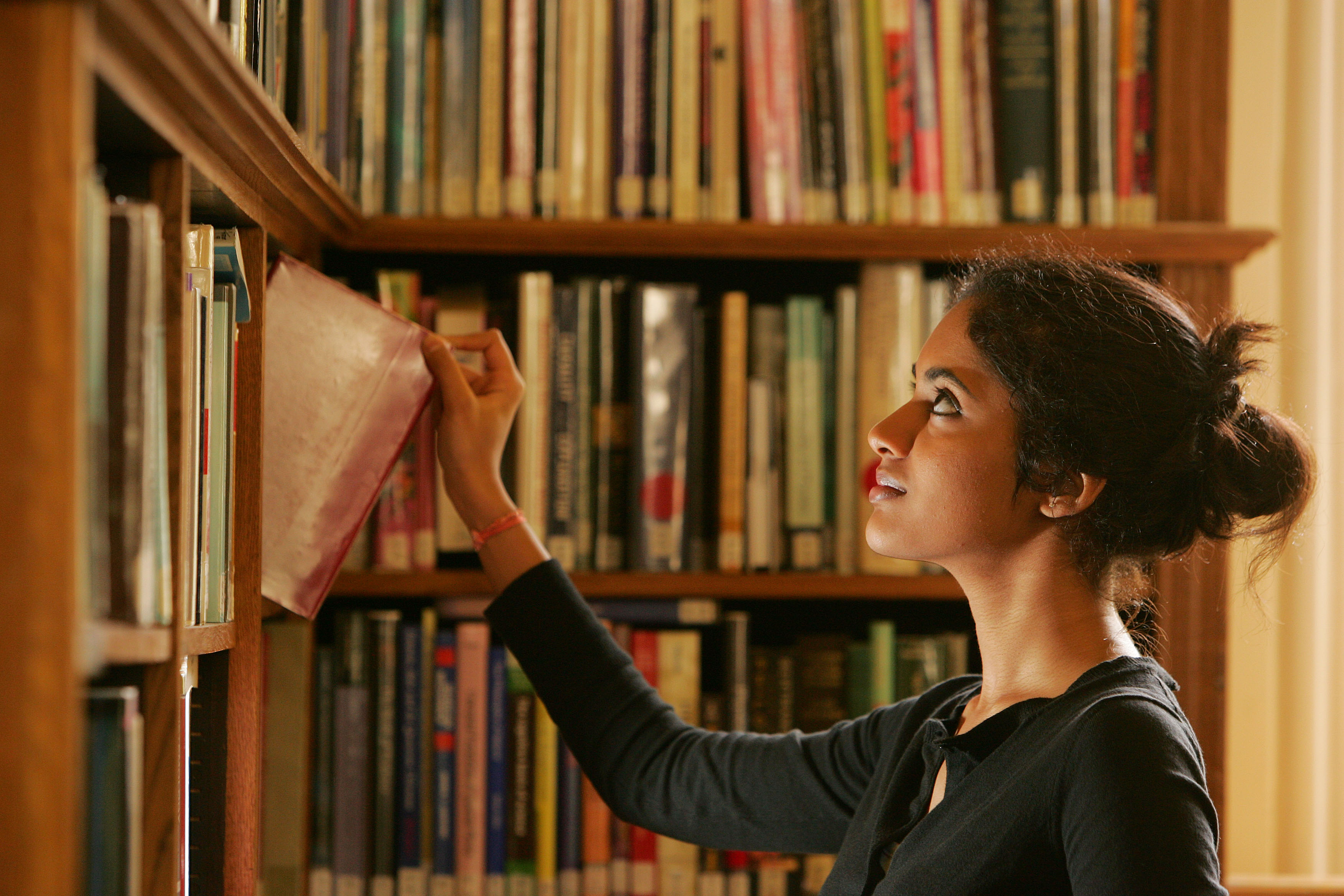 Photo of a student in the library choosing a book from the shelf