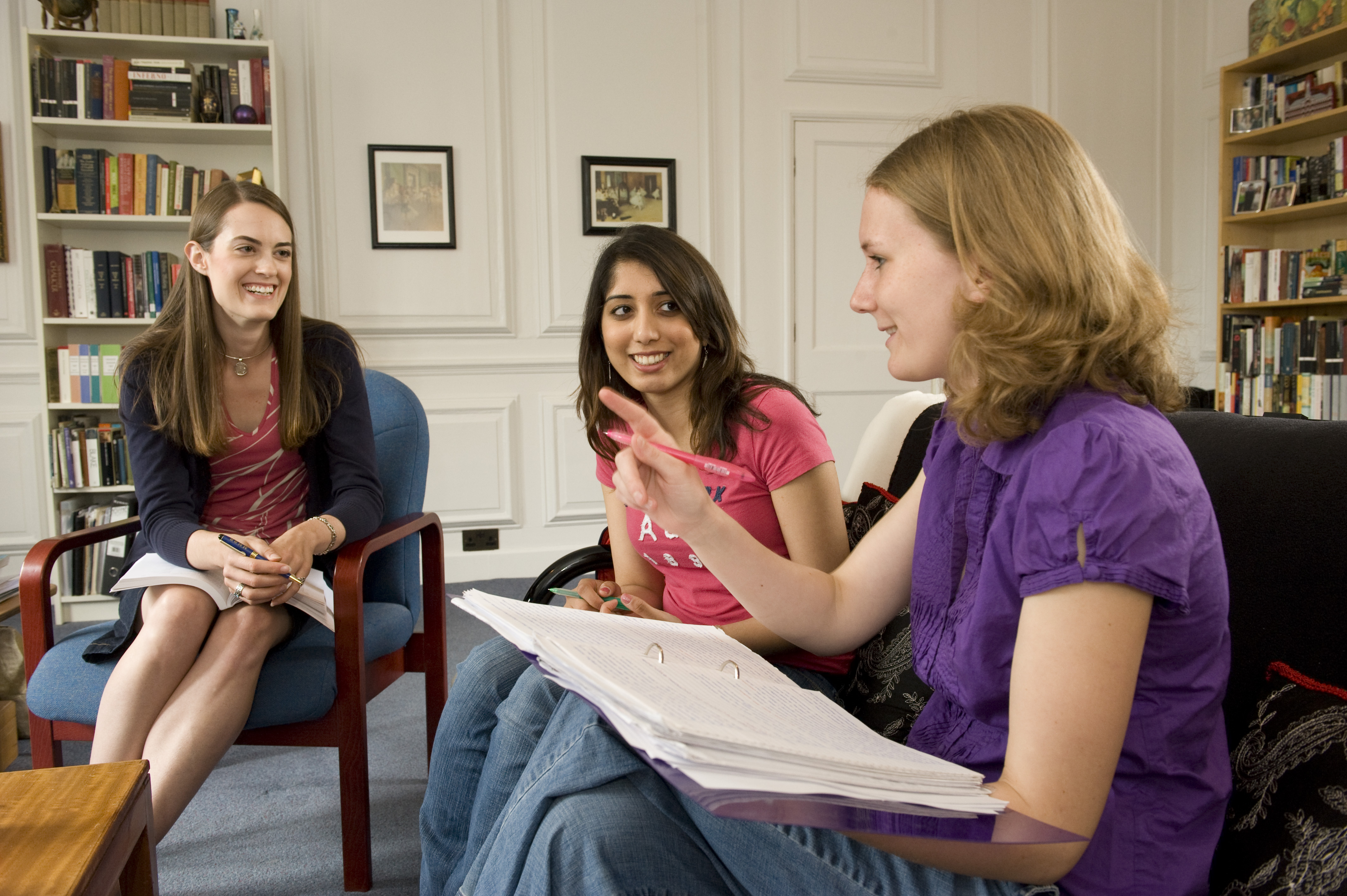 Photo of three students sat down conversing in a study