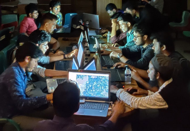 People sitting round a table at night, their faces lit up by the laptop screens in front of them