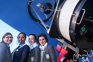 Four students standing next to an Observatory telescope