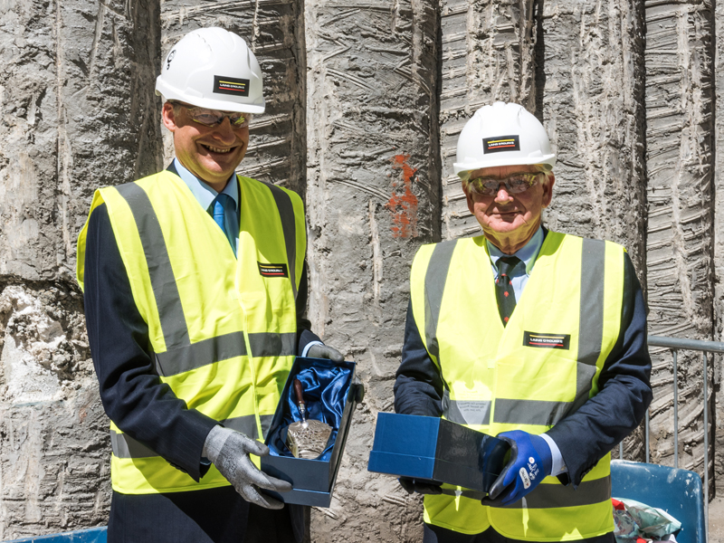 Professor John Wheater and Adrian Beecroft holding engraved silver trowels. Photo by the University of Oxford