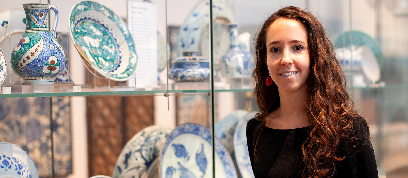 Dr Federica Gigante standing in front of display of Islamic ceramics at the Ashmolean Museum