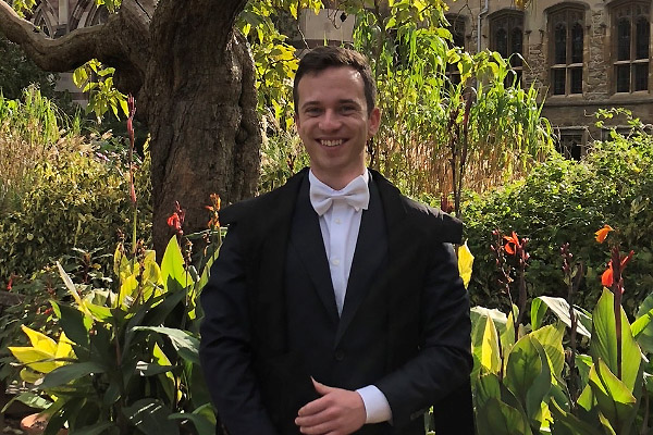 Saven Scholar Jan Berge dressed in sub fusc in the grounds of Balliol College in Oxford