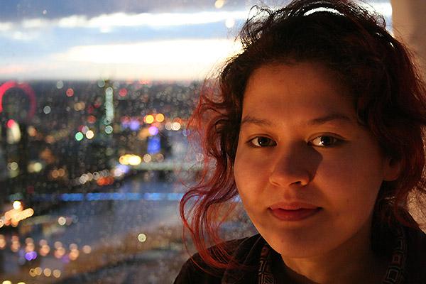 DeepMind Scholar Mizu-Nishikawa Toomey with a night-time city scape behind her