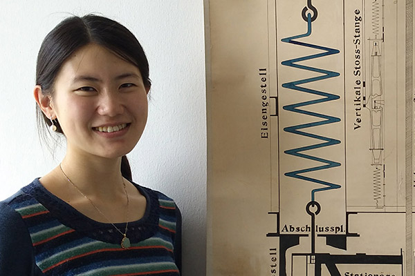 DPhil scholarship student Qi Ou standing next to a design of an early seismometer at the University of Hamburg
