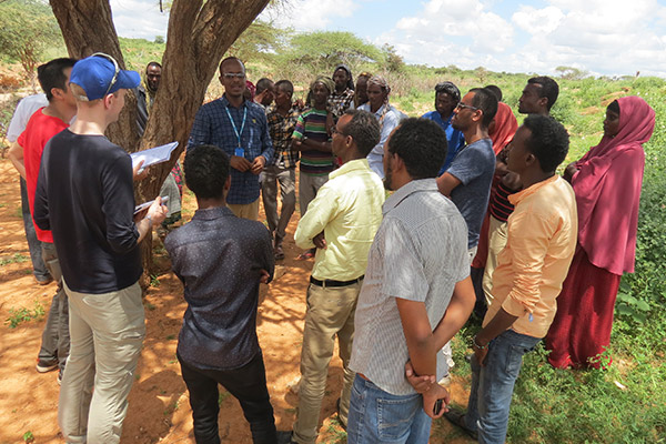 Alex Betts with about 20 refugees, standing in a circle around him, in the Dollo Ado refugee camps in Ethiopia