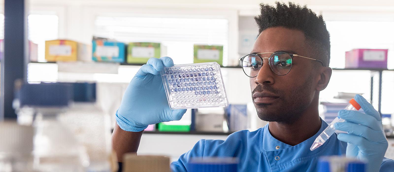 A COVID-19 vaccine researcher using scientific equipment in an Oxford University laboratory