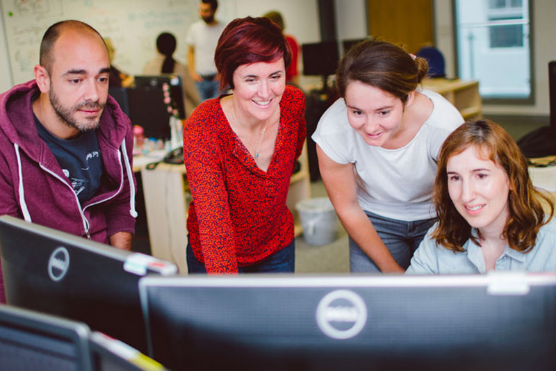 Four graduate computer science students gather around a computer monitor in a lab