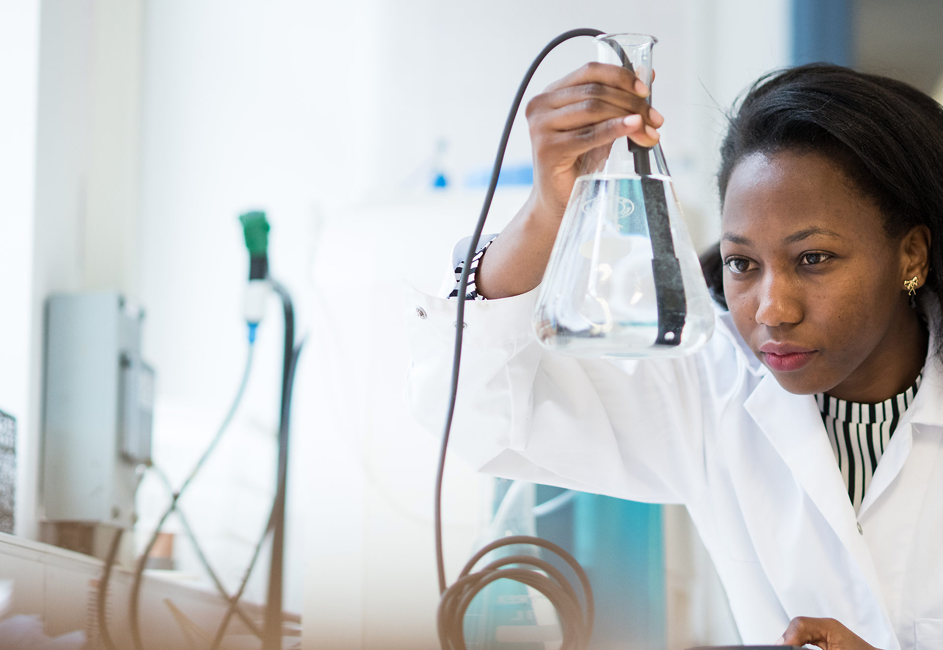 Claire Nakabugo in a white lab coat looking at vessel containing water in the lab during her master's course at Oxford