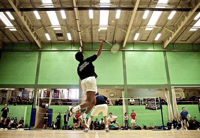 Photo of a badmington player jumping for a smash in a doubles match