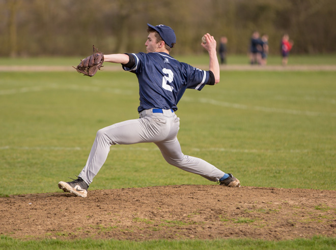 Close-up photo of a pitcher, mid-throw on the mound