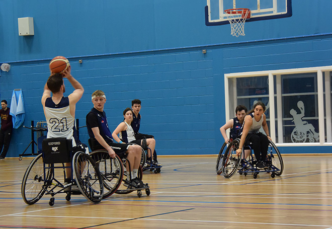 Photo of basketball player preparing for a 3-point shot in a wheelchair basket ball game