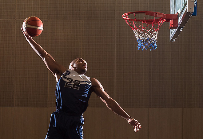 Photo of basketball player performing a windmill slam dunk