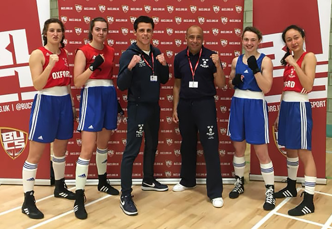 Photo of four female boxers stood along side coaches all facing the camera with their fists up and smiling