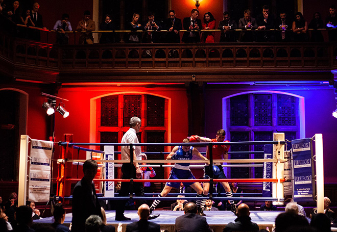 Photo of a live boxing match staged in a college hall with spectators sat around the ring and above stading on a balcony