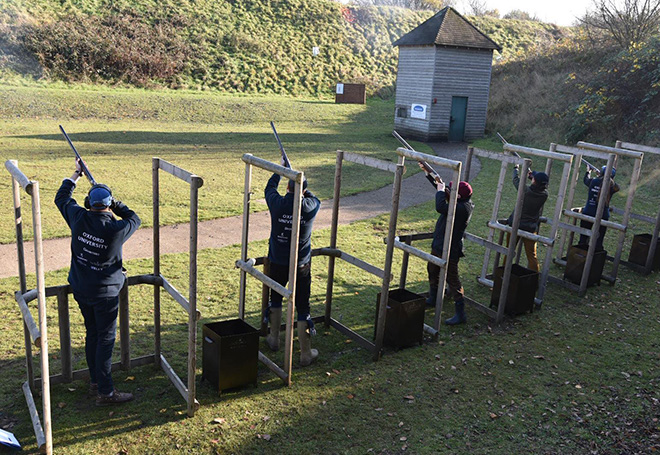 Photo of a group of shooters in seperate stalls all aiming to the sky ready to shoot